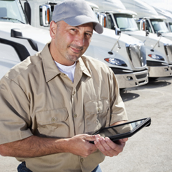 Driver with tablet in front of fleet of trucks
